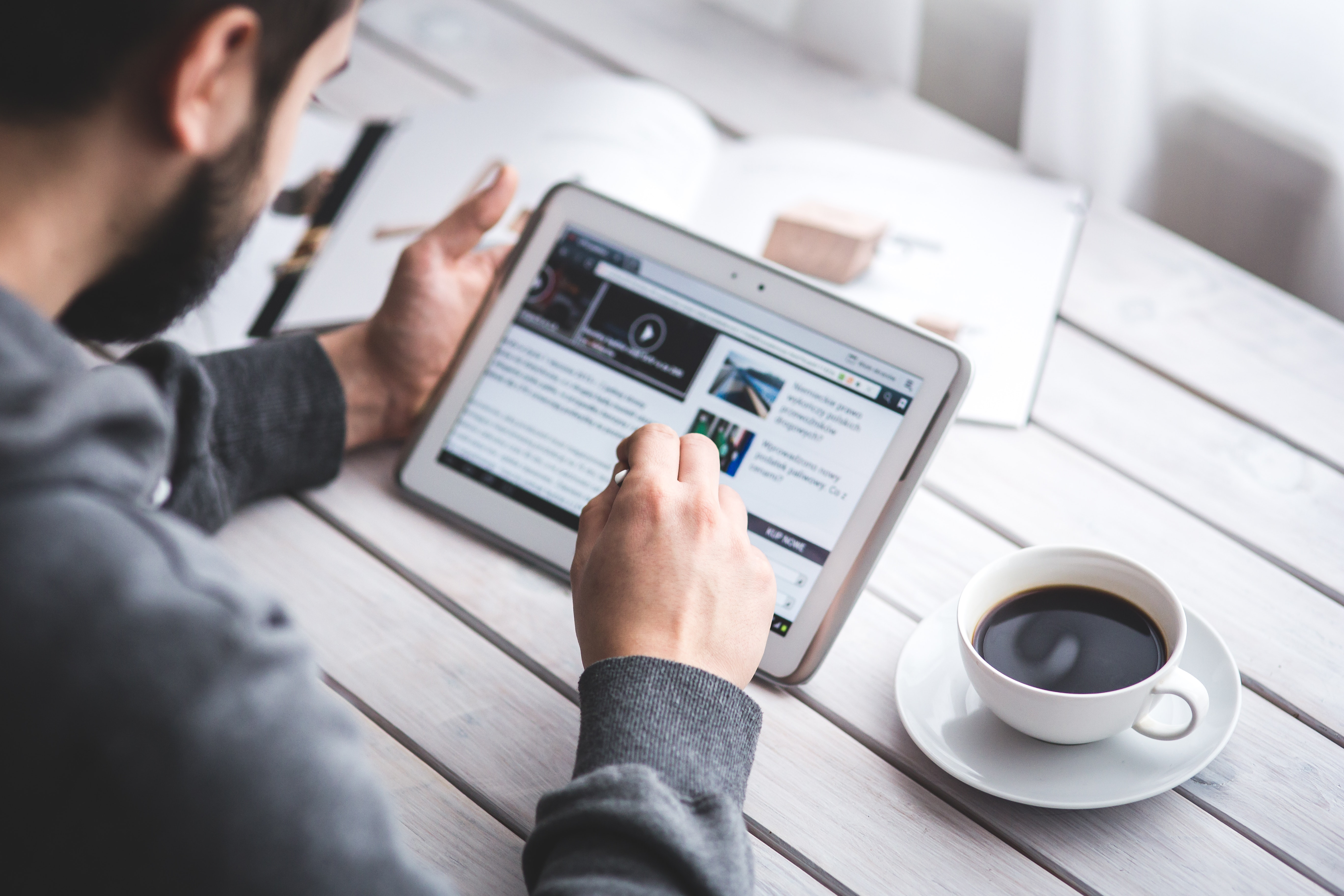 Man reading website content on tablet - providing the best user experience